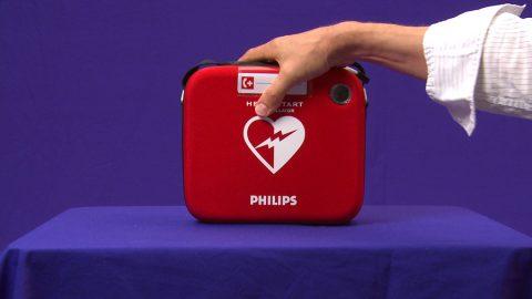 Defi. Wir nehmen das Zupacken beim Defi auf. Später soll das so aussehen, als nähme der Helfer das Gerät aus einem Kasten heraus.