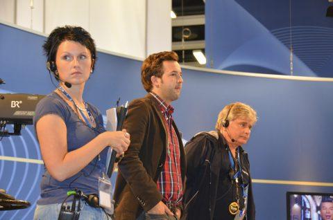 Die Drei von der Funkstelle: Aufnahmeleiterin Antje, iPhone-Jongleur Josef und Urgestein Kai lauschen dem Regisseur.