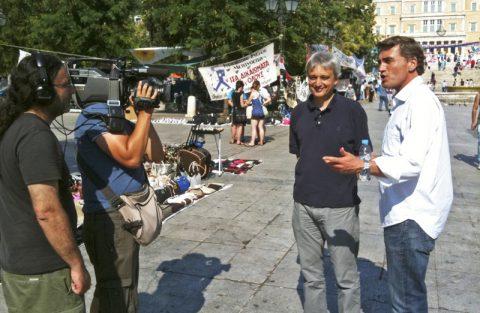 Spaziergang. Korrespondent Peter und Moderator Stefan laufen über den Syntagmaplatz, wo Volk und Politik zusammenkommen. Im Hintergrund: Das griechische Parlament.