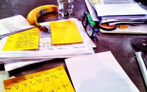 Typischer Moderatoren-Arbeitsplatz für 8-Stunden-Livesendungen: Ein gelber gebogener Energieriegel, Puder und jede Menge Zettelkram...