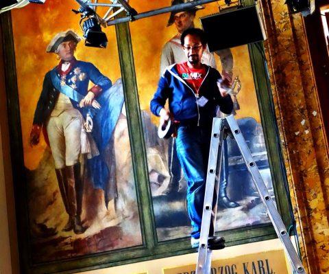Ein Mitarbeiter trägt fast Partnerlook mit den historischen Figuren an der Wand... ;-)