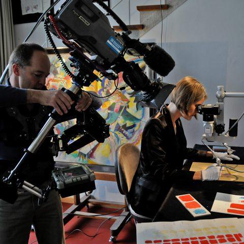 Chef-Restauratorin Iris Winkelmeyer begutachtet für unsere Kamera einen Farbtupfer von Kandinsky.