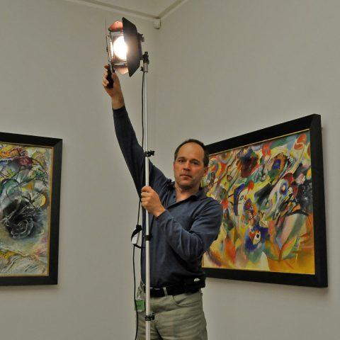 Stephan richtet das Licht ein - mit großer Vorsicht, denn die Ölbilder vertragen keine Scheinwerfer...